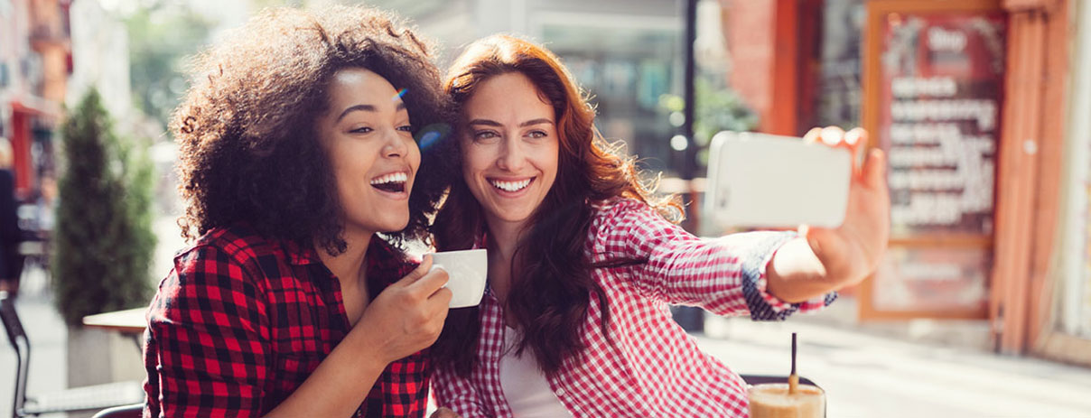 woman taking selfie with a smart phone with another woman holding a mug