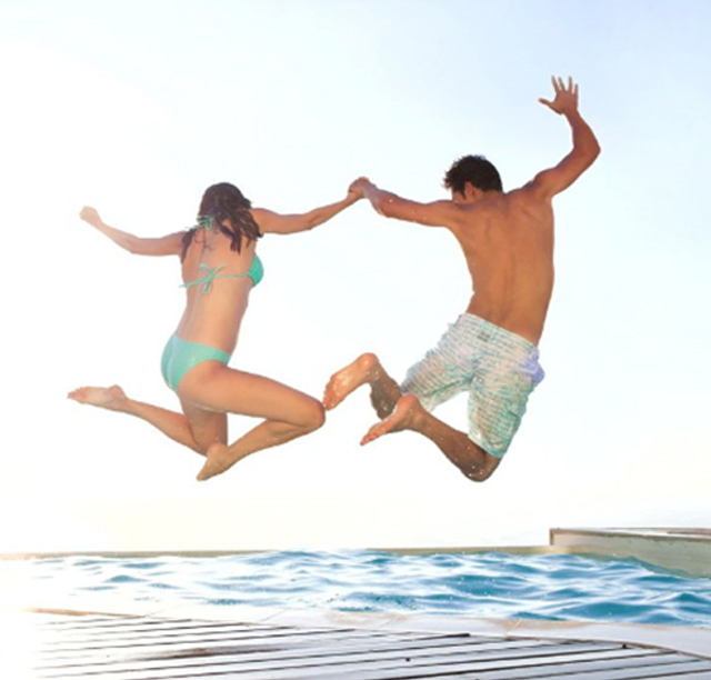 Man and woman jumping into pool