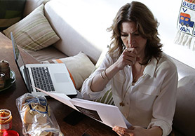 Woman reading and contemplating with laptop
