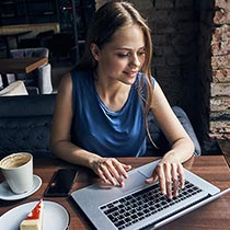Young woman working on her laptop while drinking coffee and eating a piece of cake