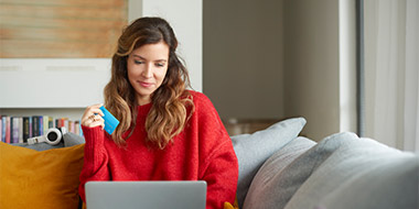 Woman on couch holding credit card and laptop