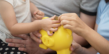 Parent and child putting money in a piggy bank