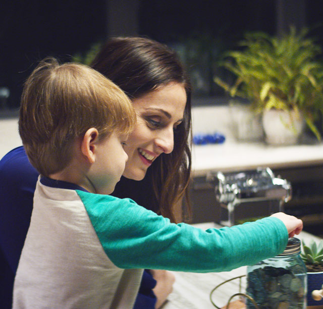 Farnoosh and son putting coins in a jar in the kitchen