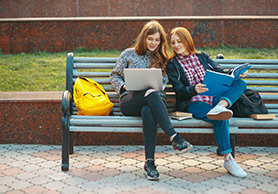 2 girls on bench with laptop