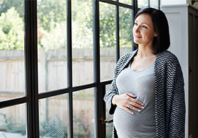 Pregnant woman looking out window