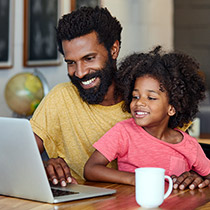 man and daughter on laptop