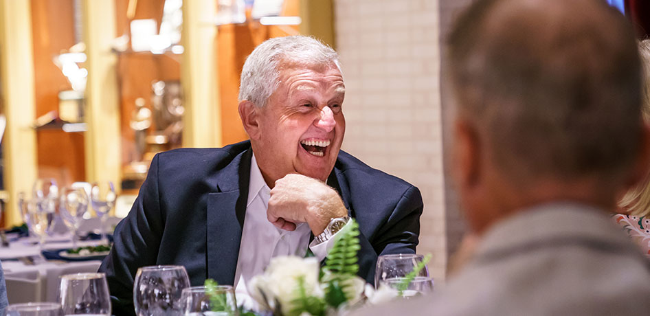 Colin Montgomerie laughing during a meal