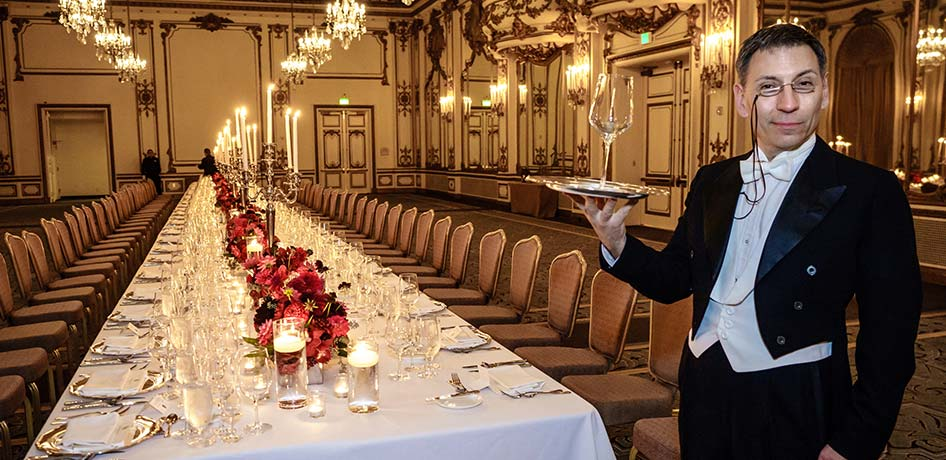 Long elegantly set dinner table with waiter in tuxedo