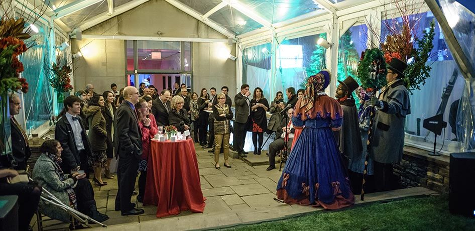 Tent with event attendees and carolers singing