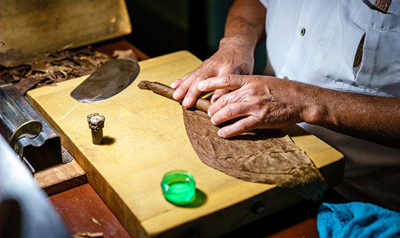 Man rolling a cigar at cigar rolling station