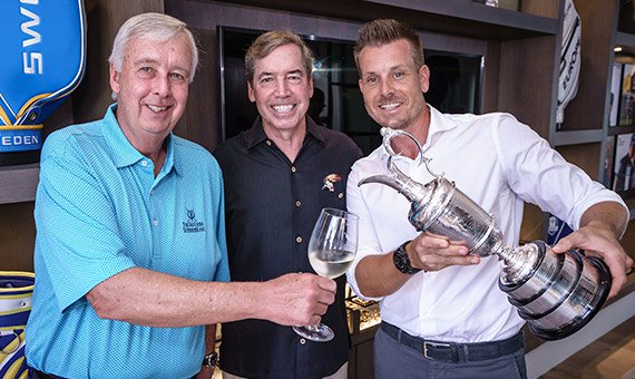 Henrik Stenson with two event attendees and trophy