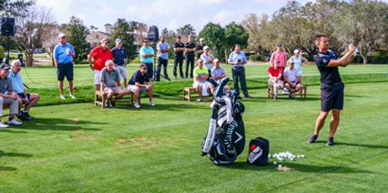Henrik Stenson on golf course with event attendees